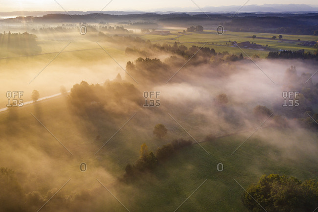 Germany- Bavaria- Geretsried- Aerial view of countryside shrouded in fog at sunrise