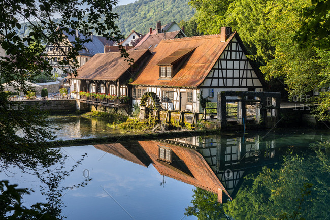 Germany- Baden-Wurttemberg- Blaubeuren- Countryside cottages reflecting in shiny river