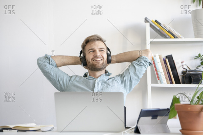 Smiling man listening to music at desk in office