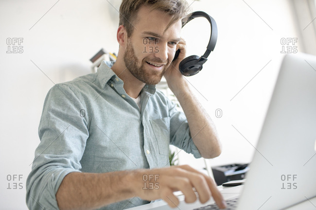 Smiling man with headphones and laptop at desk in office