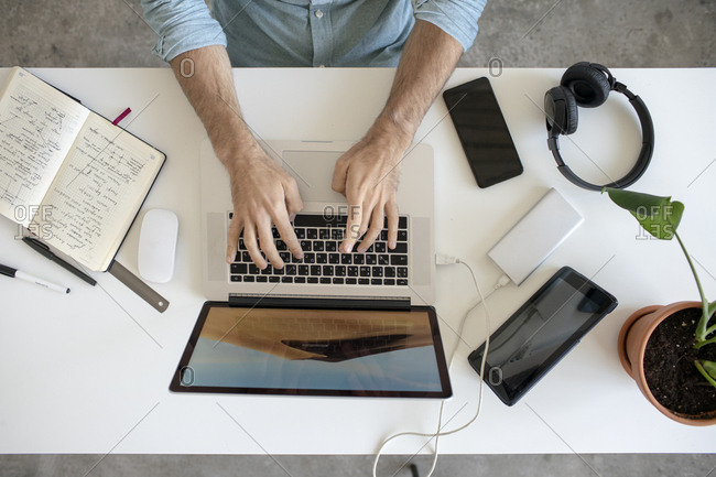 Top view of man using laptop at desk in office