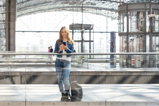 Woman using smartphone at the train station- Berlin- Germany