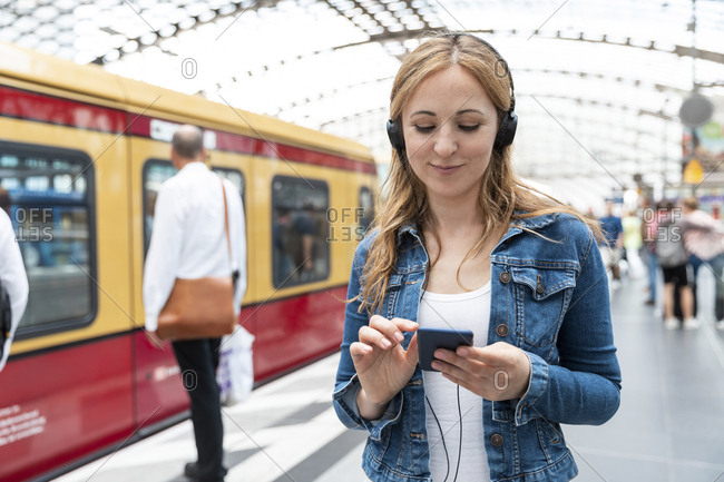 Smiling woman with smartphone and headphones on the station platform- Berlin- Germany