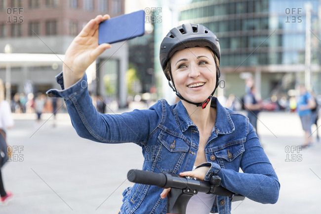 Smiling woman with e-scooter taking a selfie in the city- Berlin- Germany