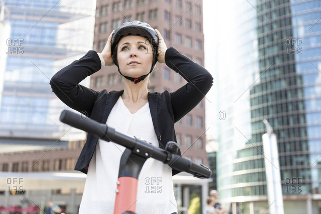 Woman with e-scooter in the city putting on helmet- Berlin- Germany