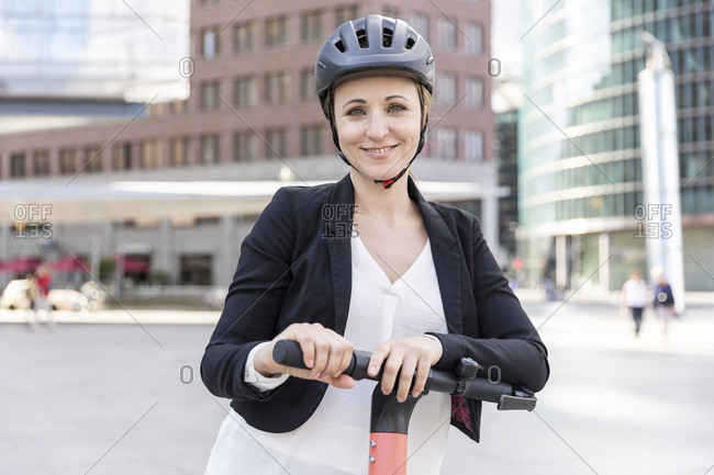 Portrait of smiling woman with e-scooter in the city- Berlin- Germany