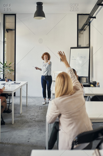 Businesswoman raising her hand during a workshop in conference room