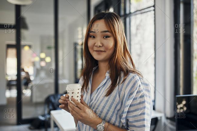 Portrait of businesswoman having a coffee break in office