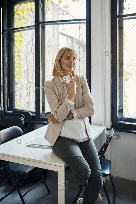 Pregnant businesswoman having a coffee break in office