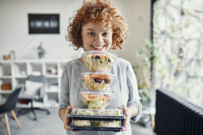 Portrait of smiling businesswoman holding stack of takeaway food in office