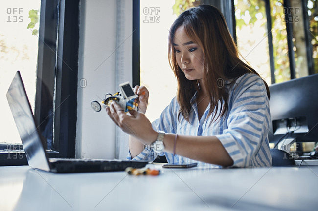 Businesswoman holding model car at desk in office