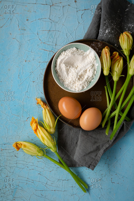 Close up of zucchini flowers, eggs, and flowers on a tray