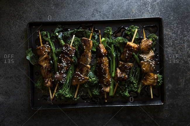 Salmon teriyaki skewers over roasted broccoli rabe