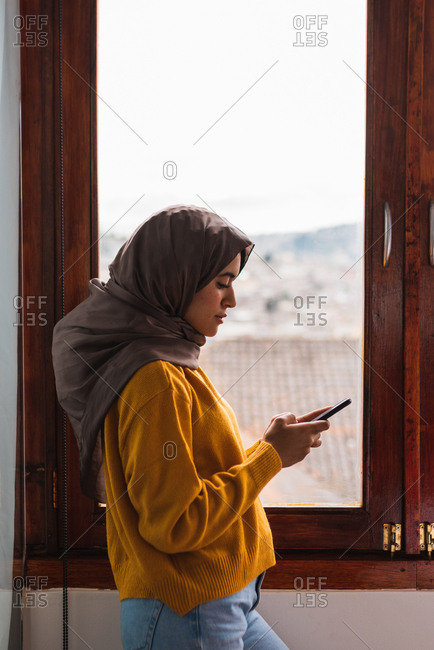 Muslim girl with hijab in front of a window using her phone
