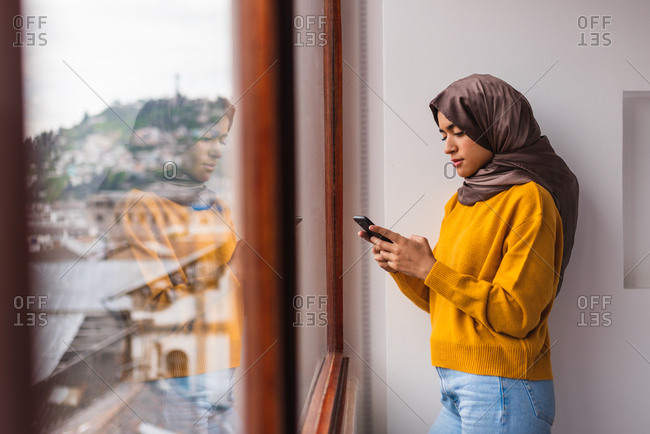 Muslim girl with hijab in front of a window texting on her phone