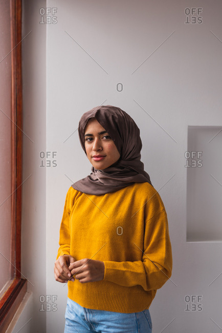 Portrait of a Muslim girl wearing hijab and a yellow sweater and jeans