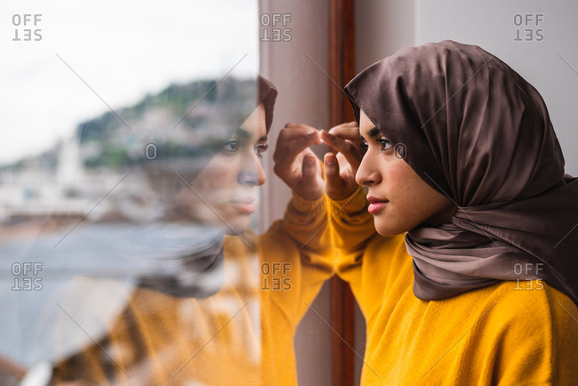 Young Muslim girl with brown hijab and yellow sweater looking out of the window