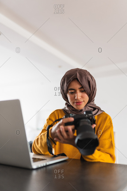 Young Muslim girl sitting with a camera in her hand in front of a laptop computer