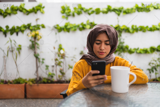 Young Muslim girl sitting in an inner courtyard with plants using her mobile phone