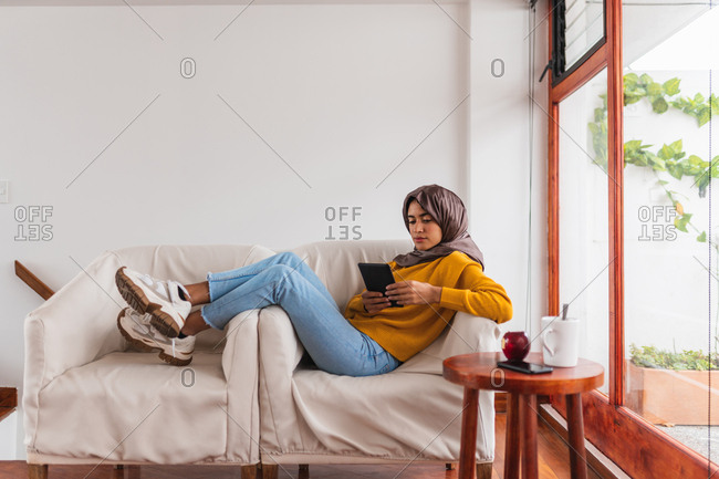 Young Muslim girl sitting on a sofa with a tablet
