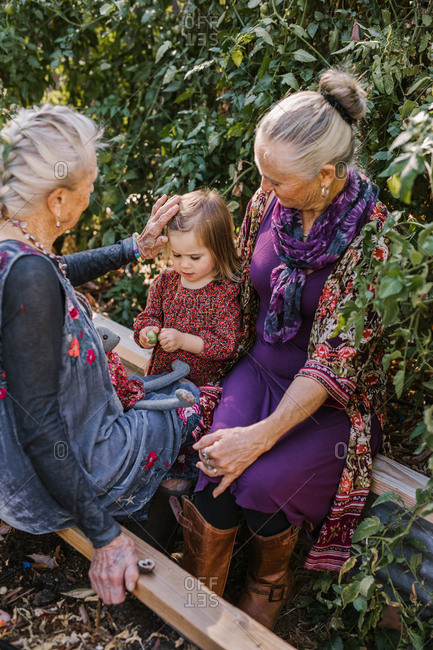 Two elderly women sit with a little girl in a garden, while the older woman pushes some hair out of her face
