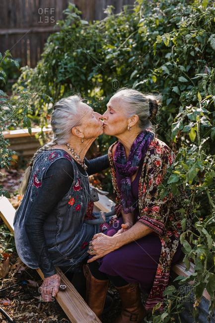 An elderly woman kisses her daughter in a garden