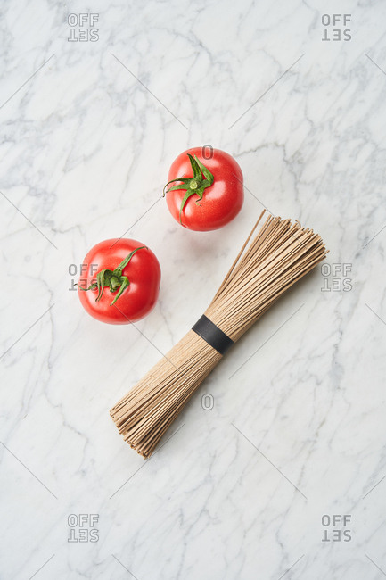 Two tomatoes on white marble surface with bundle of whole grain pasta