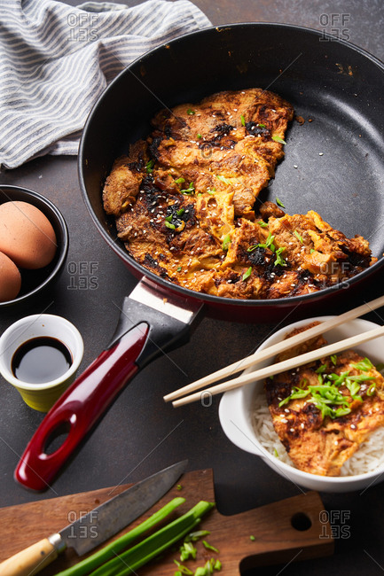 Overhead view of egg foo young dish being prepared in a skillet