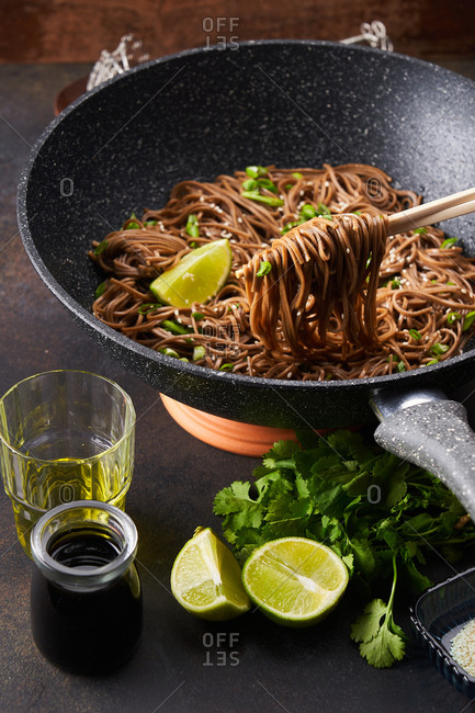 Sesame noodles in a skillet with chopsticks