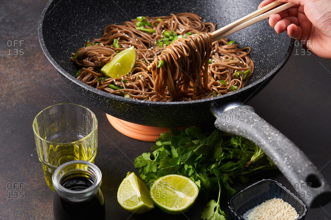 Hand holding chopsticks with sesame noodles from a skillet