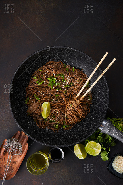 Overhead view of sesame noodles in a skillet with chopsticks