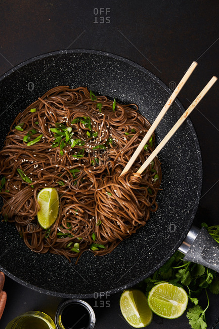 Top view of sesame noodles in a skillet with chopsticks