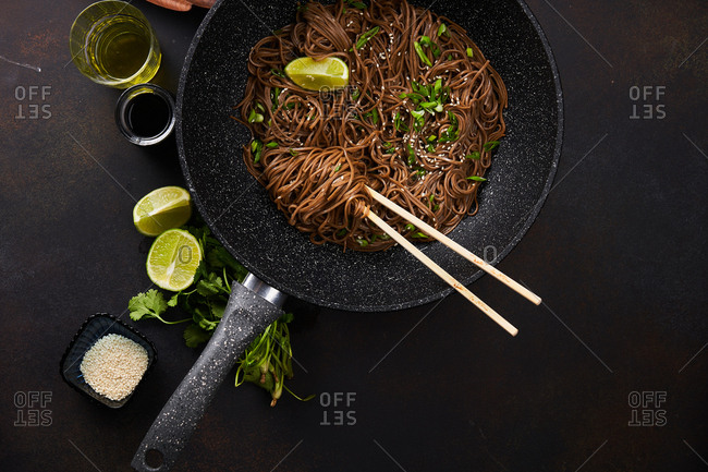 Top view of sesame noodles in a wok with chopsticks