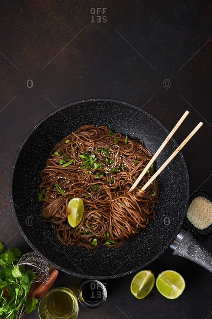 Overhead view of sesame noodles in a wok with chopsticks