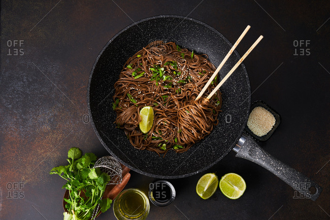A wok with sesame noodles and chopsticks