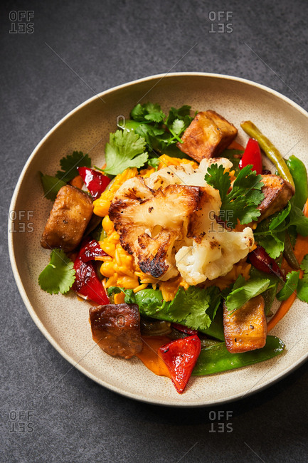 Colorful dish with grilled cauliflower and other veggies