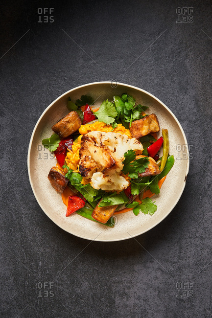 Overhead view of a colorful dish with grilled cauliflower and other veggies