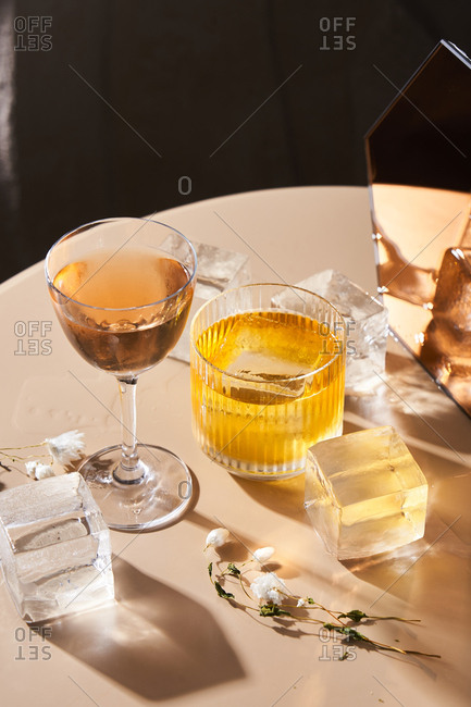 Cocktails beside cube shaped ice cubes and mirror