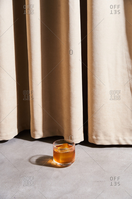 Cocktail with large ice cubes by beige drapes