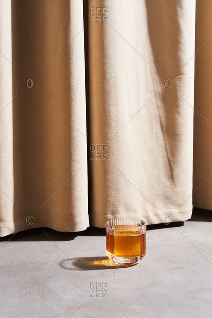 A cocktail with large ice cubes by beige drapes