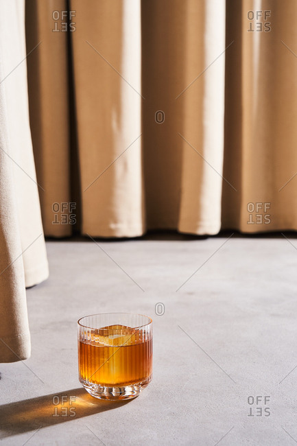 Golden colored cocktail with large ice cubes by beige drapes