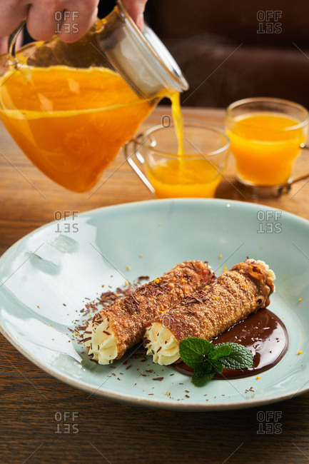 Person pouring orange juice beside dish with delicious cannolis