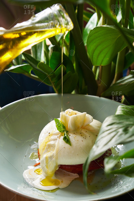 Oil being poured over a gourmet poached egg dish