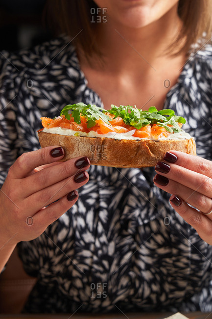 Woman eating toast topped with salmon