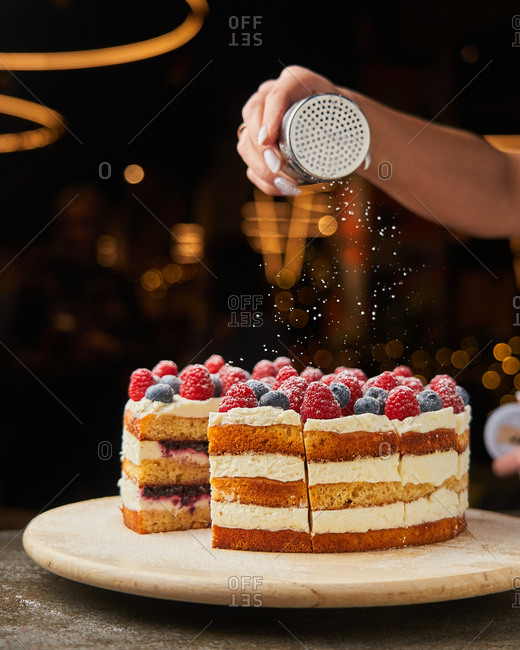Baker sprinkling powdered sugar over a cake with berries on top