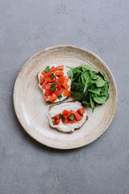 Overhead view of vegan bruschetta with hummus and tomato