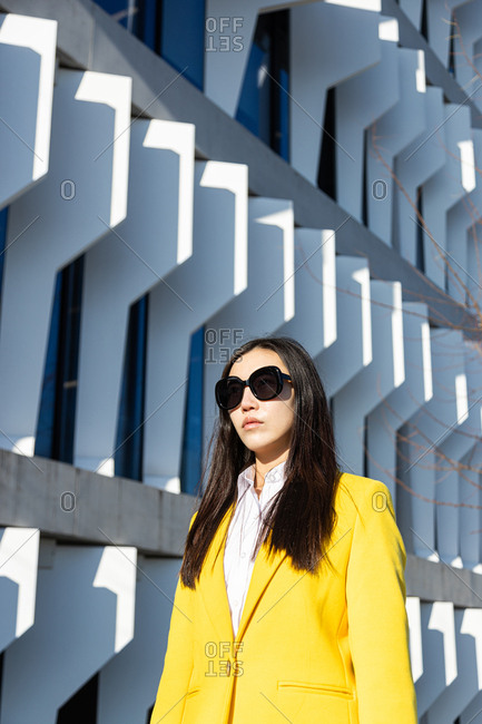 Asian business woman with yellow coat walking down street with building in the background