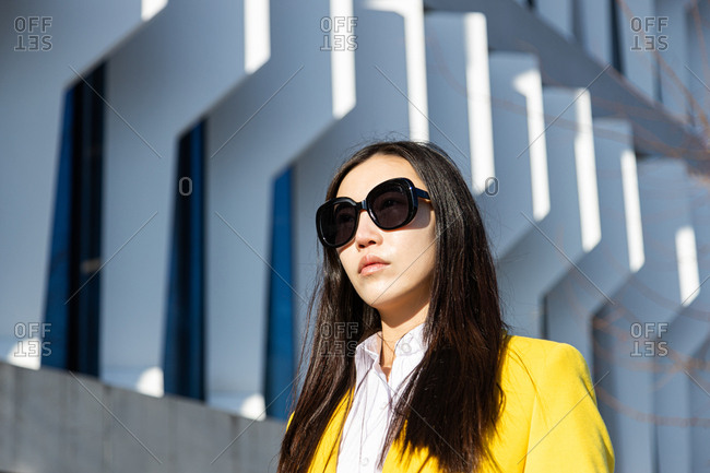 Close up of Asian business woman with yellow coat walking down street with building in the background