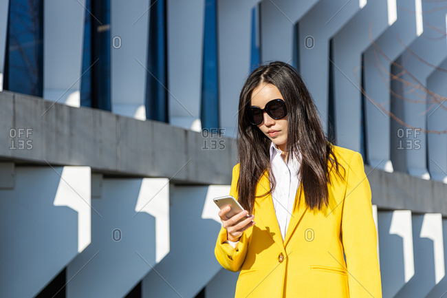 Asian business woman with yellow coat and smart phone walking on street with building in the background