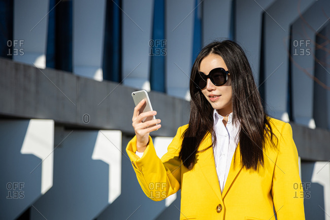 Asian business woman with yellow coat and smart phone walking on the street with building in the background